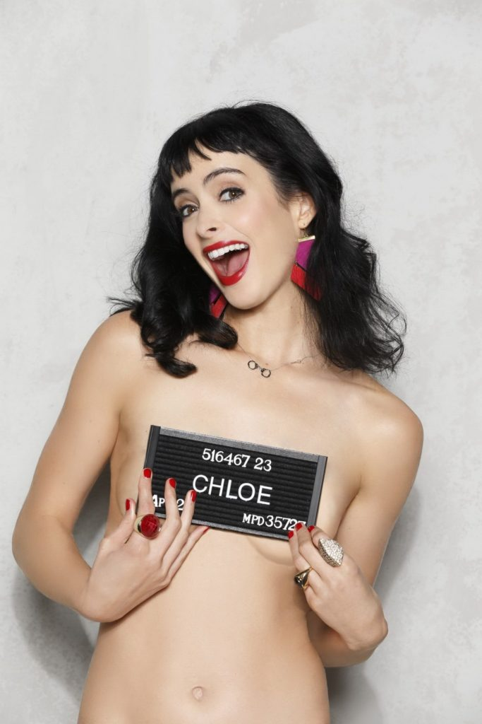 The singer Krysten Ritter holding a sign over her boobs