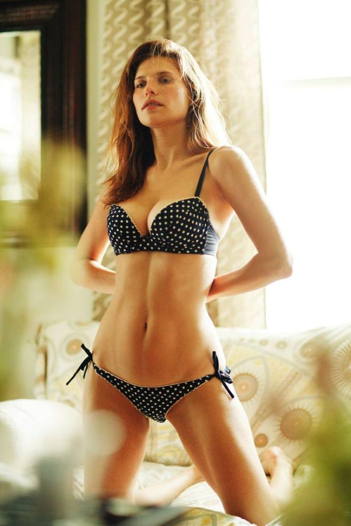 Lake Bell kneeling on couch in polka dot bikini