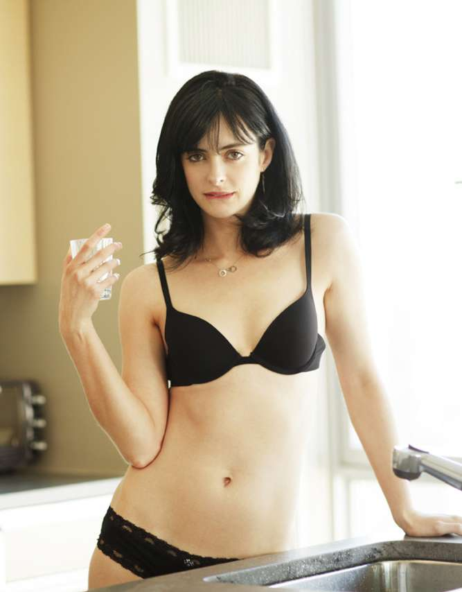 The talented Krysten Ritter holding a glass of water in her black underwear