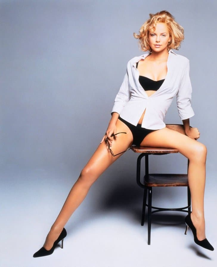 Charlize Theron in panties and open white shirt on desk