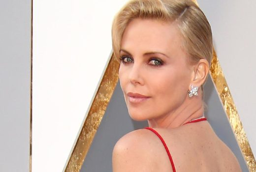 Charlize Theron looking back at camera at award show and looking gorgeous