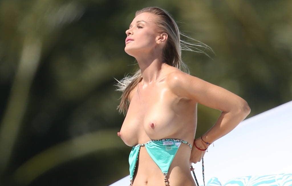 The superstar Joanna Krupa taking her bikini top off at the beach