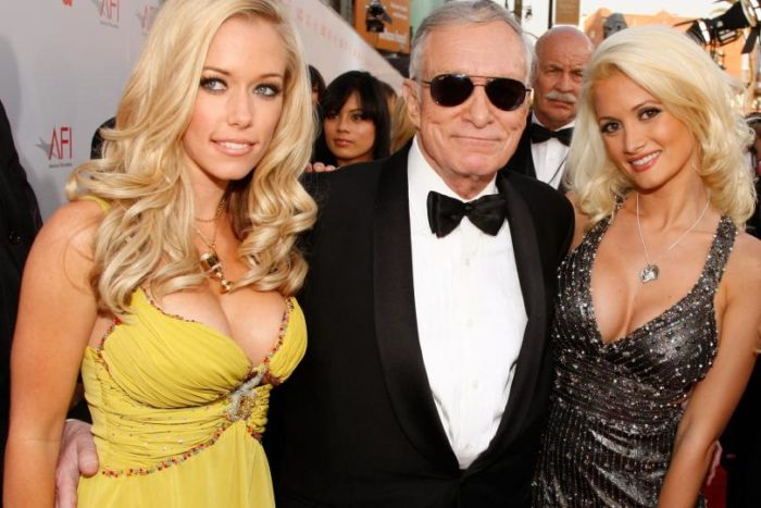 Kendra Wilkinson and Holly in a yellow dress next to Hugh Hefner
