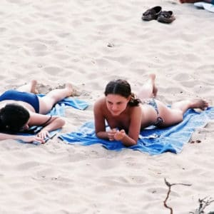 star Natalie Portman laying on a blue towel showing some cleavage