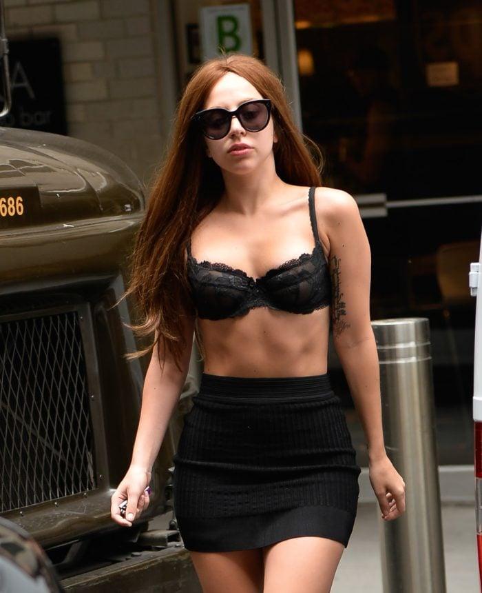 The celebrity Lady Gaga in black bra, skirt and sunglasses
