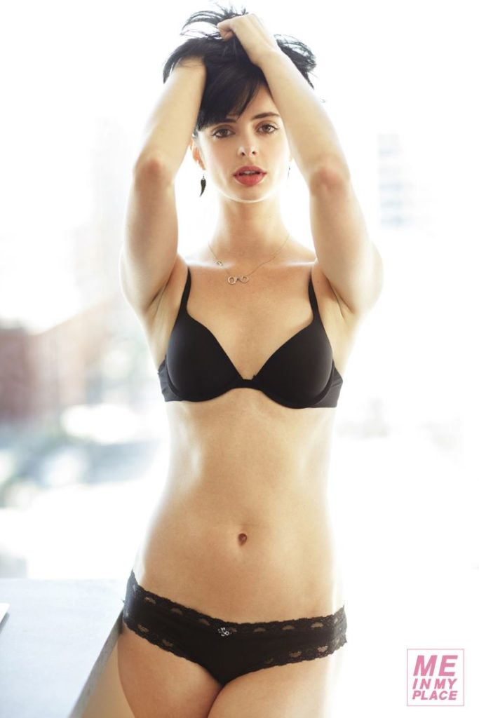The actress Krysten Ritter in black underwear holding her hair up