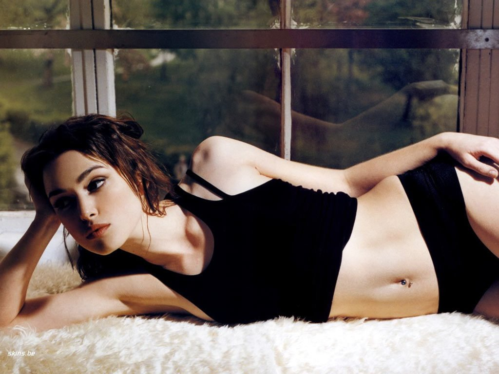 The celebrity Natalie Portman in black tank top laying on white fur rug
