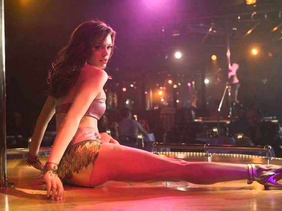 the actress Rose McGowan stripping in gold shorts and heels