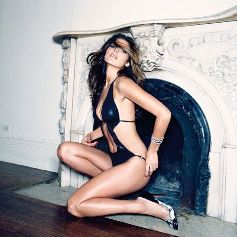Lake Bell in weird black bikini and heels in front of a fireplace