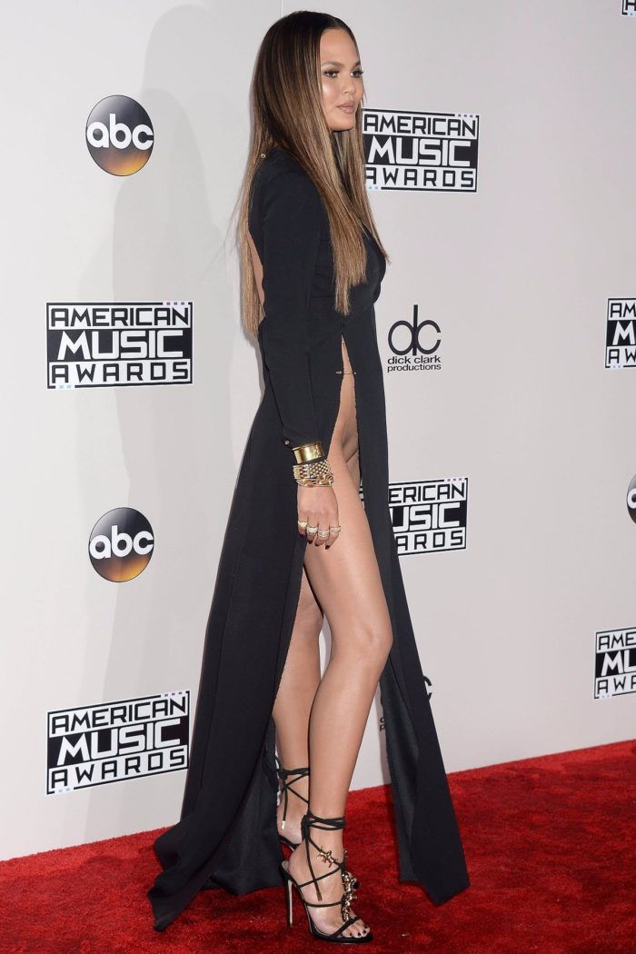 American Music Awards 2016 Chrissy Teigen shows her long legs and pussy in black gown with slit that goes above her waist