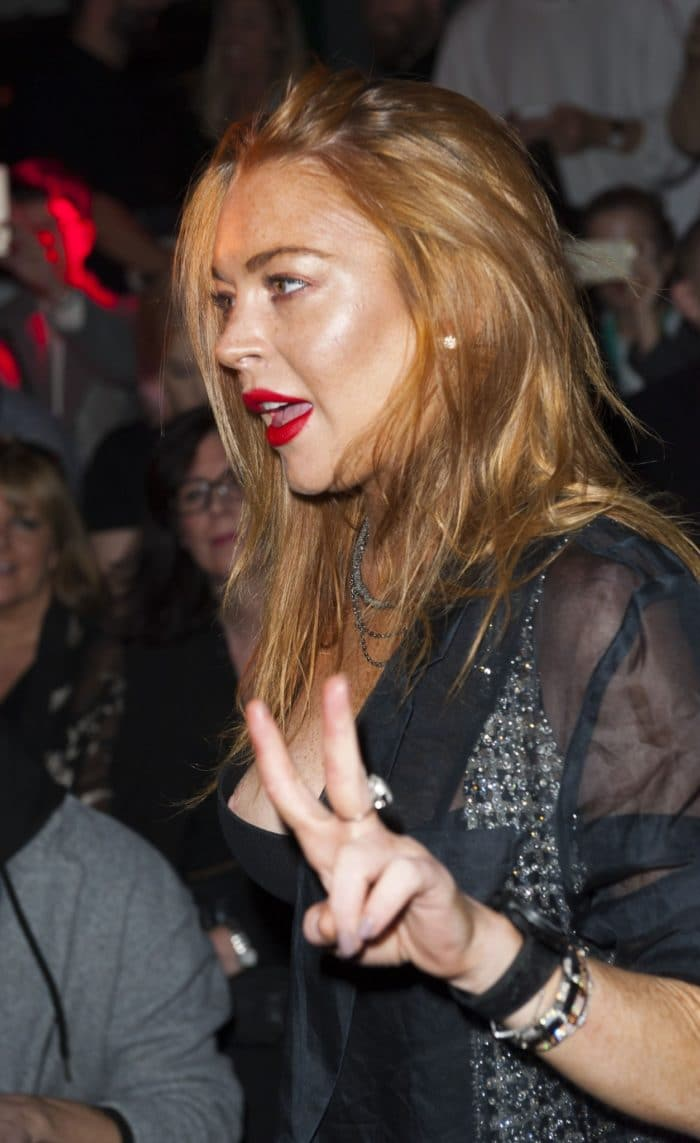 London Fashion Week photo of Lindsay Lohan and her nip-slip while she is giving a peace sign