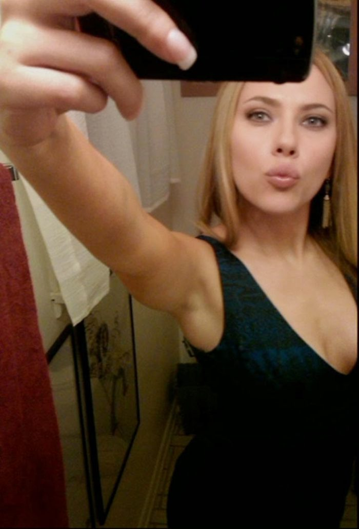 Scarlett Johansson taking a selfie in front of a mirror and making a kissy face