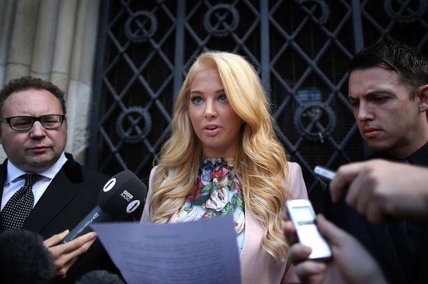 Tulisa with blonde hair reading a statement after court