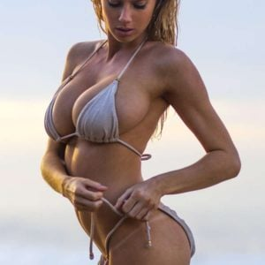 charlotte mckinney in tiny bikini looking down and sticking out her perky butt
