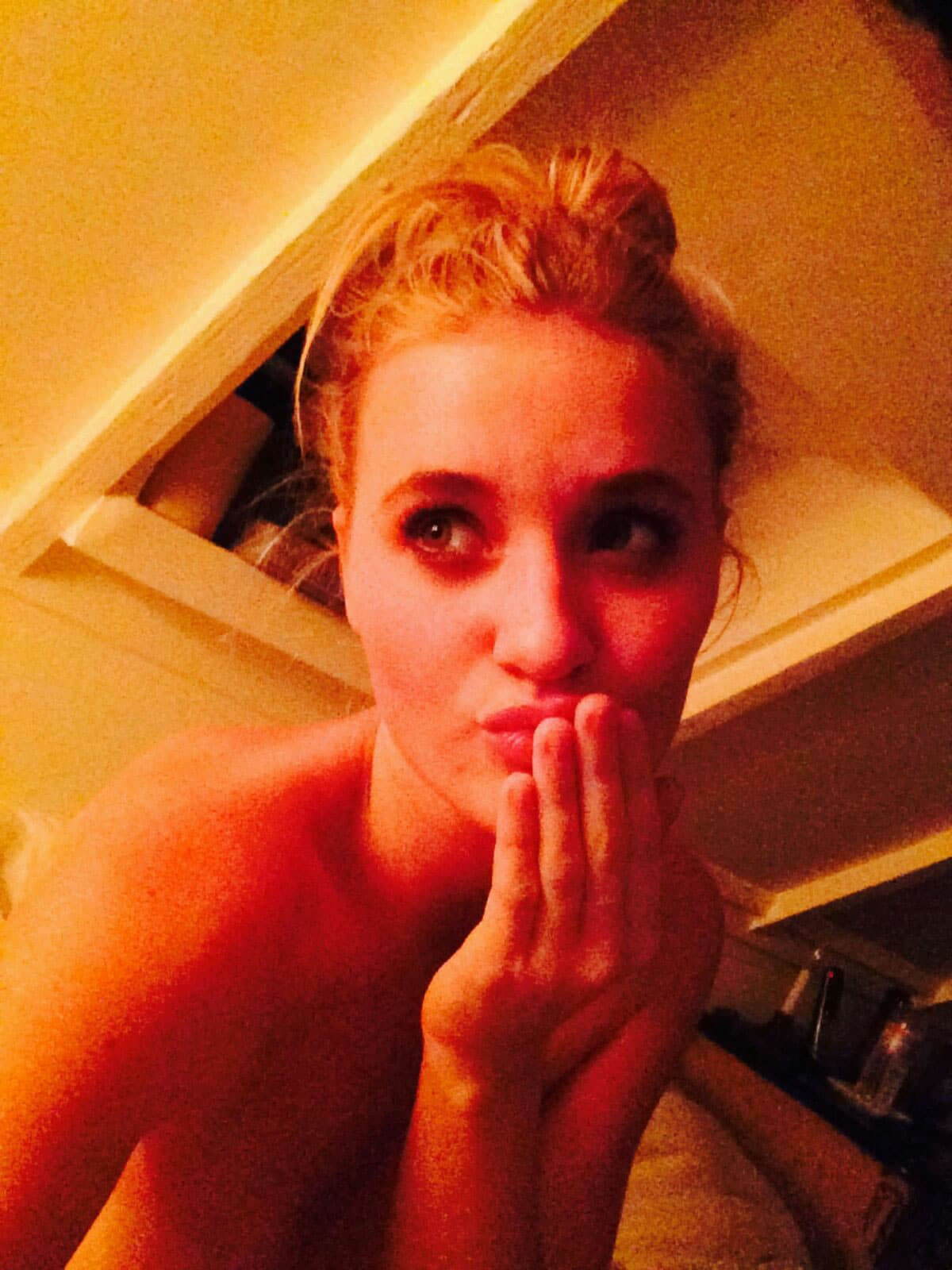 AJ Michalka taking a selfie with her hair in a bun putting hand over mouth