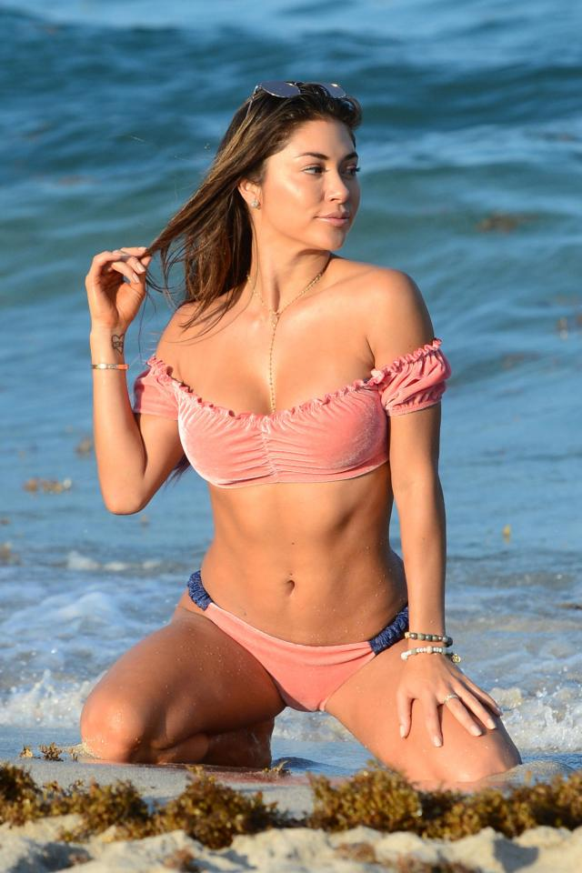 Arianny Celeste modeling in peach bikini on her knees playing with her hair