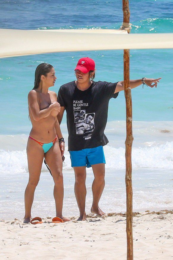 Arianny Celeste with her bikini top off at the beach