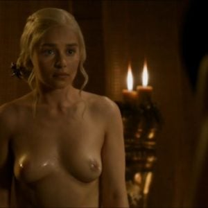 Emilia Clarke topless standing in front of candles