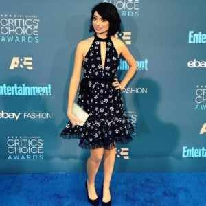 Kate Micucci in a black dress with her arm on her hip holding a clutch