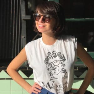Kate Micucci in a white muscle tank and sunglasses