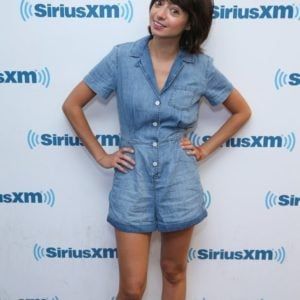 Kate Micucci wearing a jean jumper and white loafers