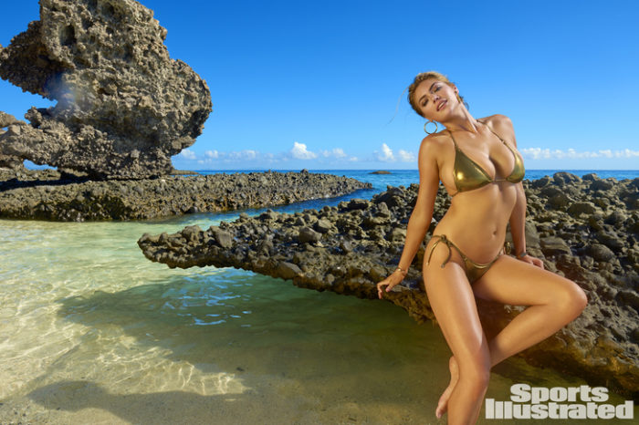 Kate Upton in Sports Illustrated photo in golden bikini sitting on a rock