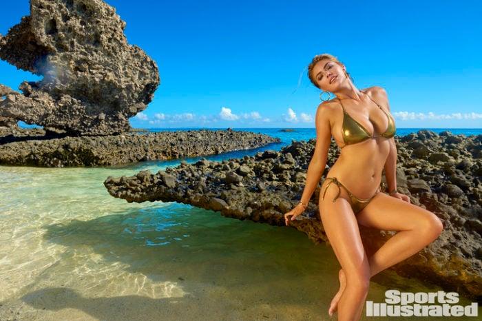 Kate Upton in Sports Illustrated photo in golden bikini sitting on a rock