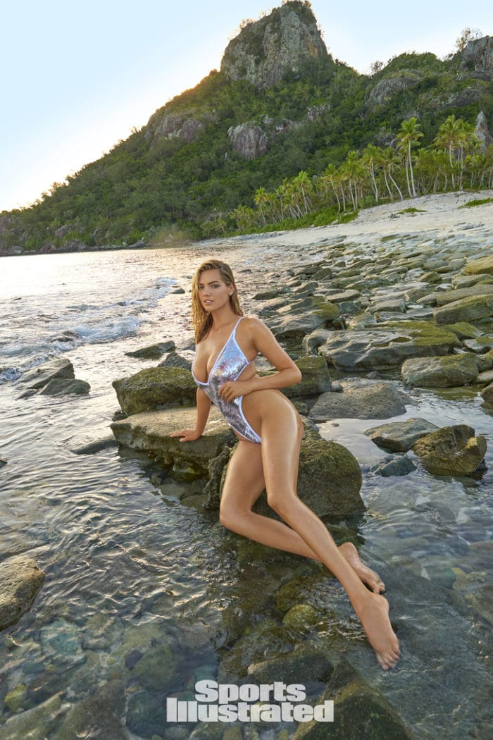 Kate Upton in silver bikini looking hot sitting on a rock