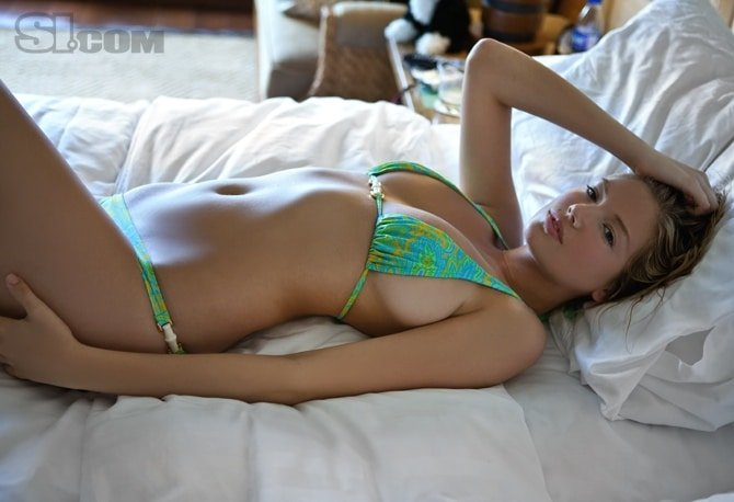 Kate Upton laying in bed with her hand on her head with a bikini on