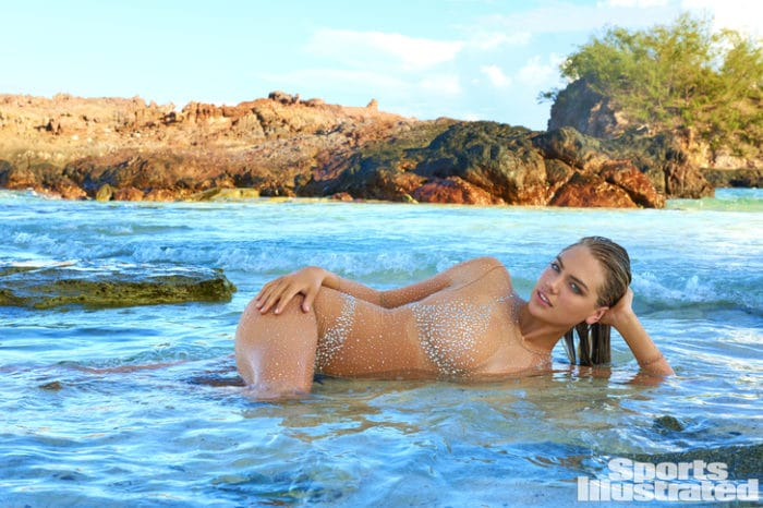 Kate Upton laying in the water with sparkly see though swimming suit on