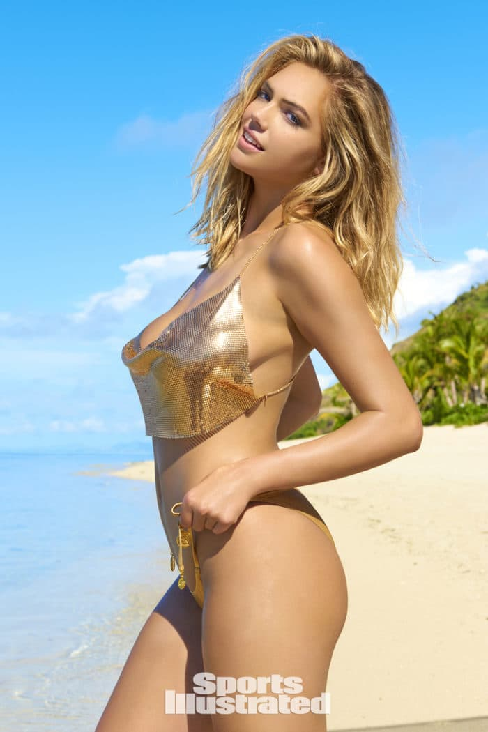Kate Upton on the beach wearing golden bikini top and pulling up her thong