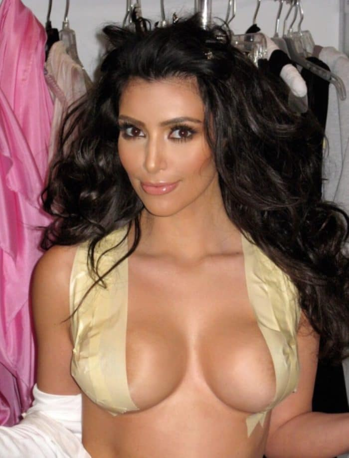 Kim Kardashians boobs popping out and finger in her mouth