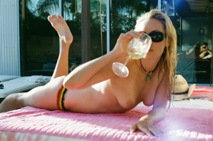 Kristana Loken taking a drink while she is laying out topless
