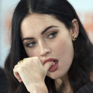 Megan Fox with finger in her mouth wearing red lipstick