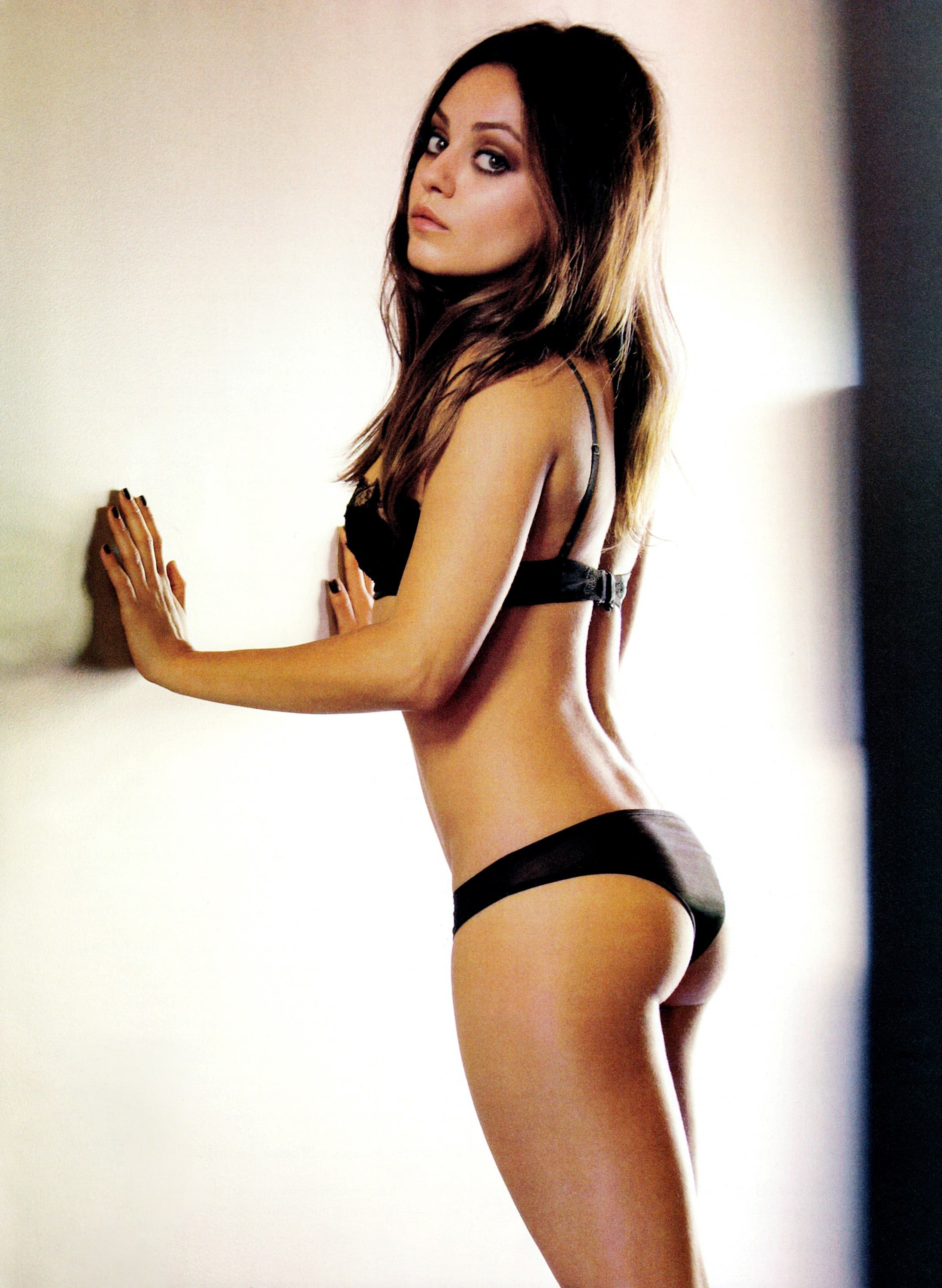 Mila Kunis in black underwear leaning against a wall
