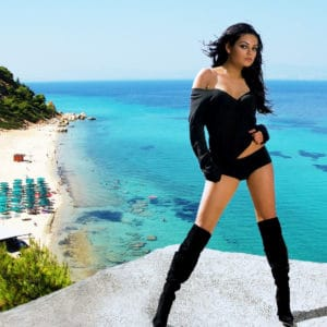 Mila Kunis standing in front of the ocean in knee high boots