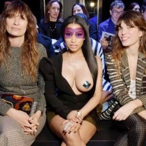 Nicki Minaj sitting down in black dress that exposes her boob during fashion week