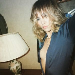 Suki Waterhouse in a blue blouse showing some side boob