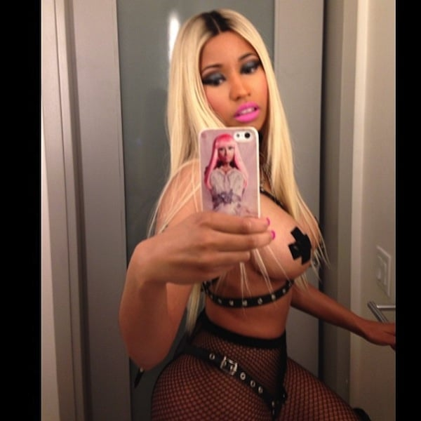 mirror selfie of Nicki Minaj with blonde hair and tape over nipple