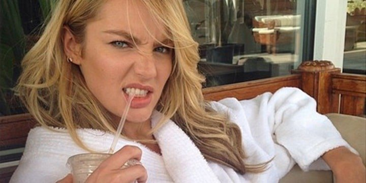 Candice Swanepoel in a robe biting on a straw