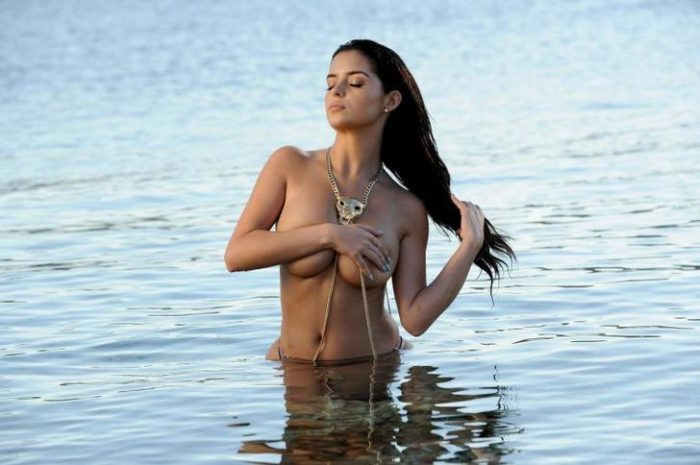 Demi Rose Mawby grabbing her hair while topless in the water