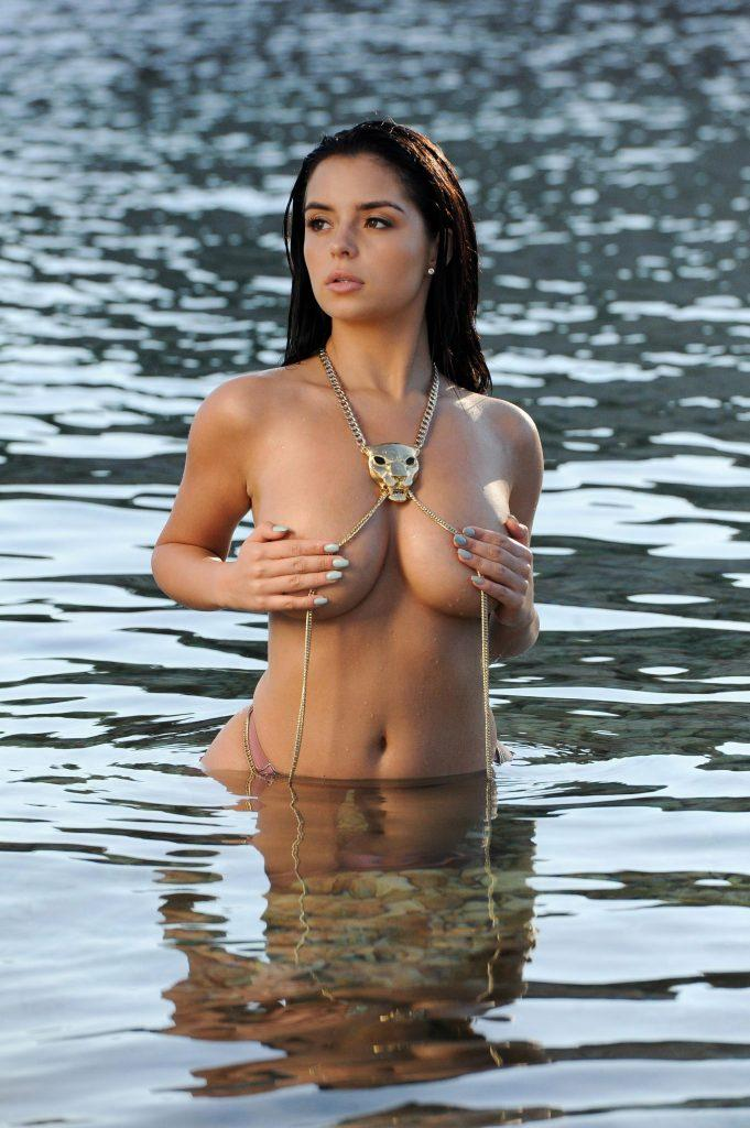 Demi Rose topless in the water with a gold chain around her neck