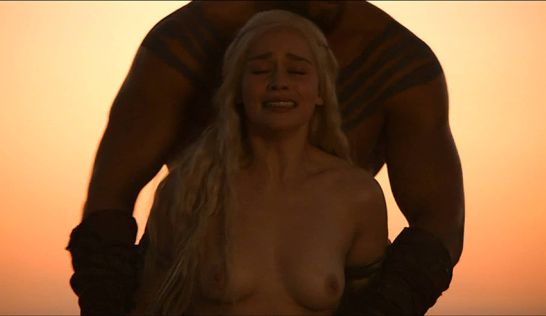 Emilia Clarke topless as she is being held back by a man