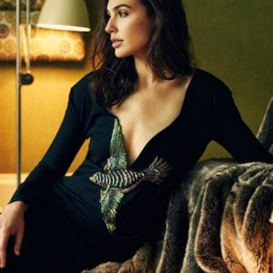 Gal Gadot in a black dress with bird print sitting on couch
