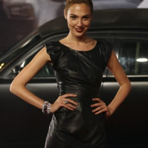 Gal Gadot in a black leather dress hands on hip
