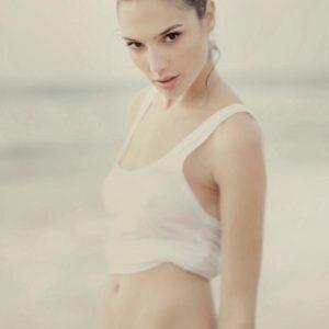 Gal Gadot in a white tank and blue bikini bottoms hair in a bun