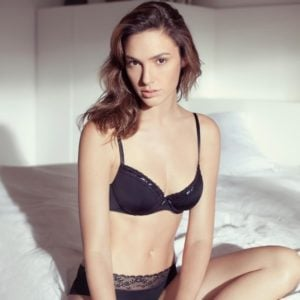 Gal Gadot in black lingerie sitting on edge of bed