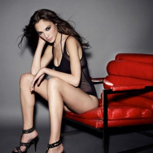 Gal Gadot sitting on a red chair in sheer body suit wearing heels