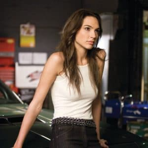 Gal Gadot with white tank top on sitting on car