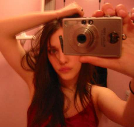Kat Dennings taking a bathroom selfie arm over head